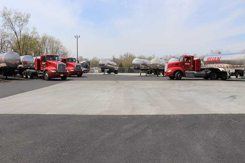 Large trucks and tanks parked in a parking lot