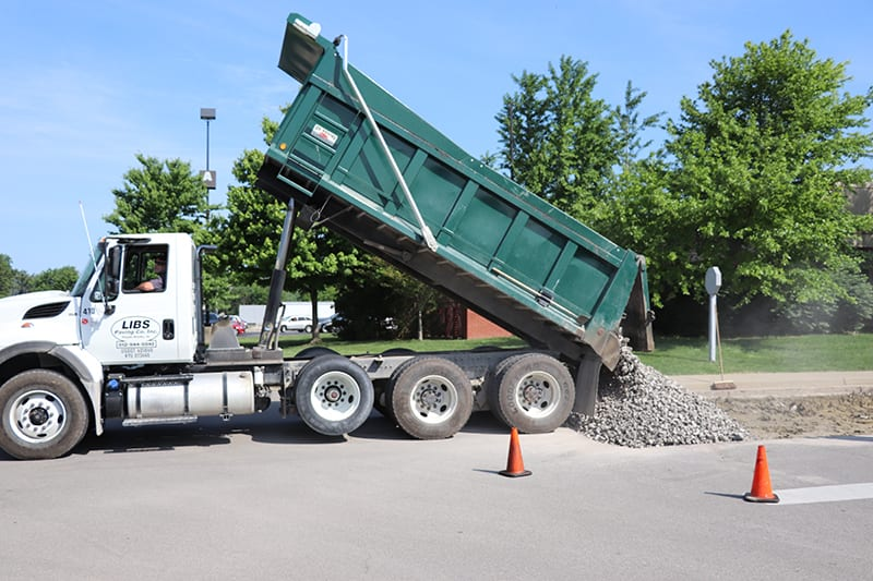 Dump Truck pouring out rocks at a construction si