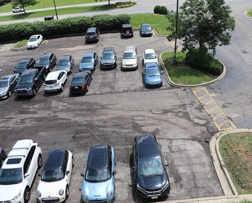 Cars parked in a parking lot that is cracked, not marked, and uneven