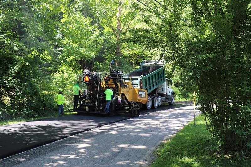 Construction workers, a truck, and a dump truck working on an asphalt paving service