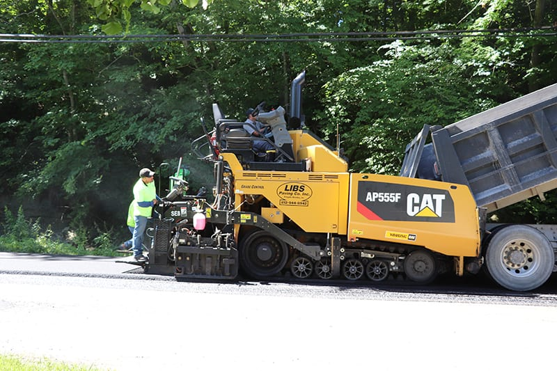 Libs Paving Co truck pouring asphalt