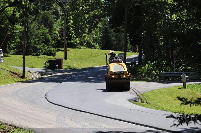 Libs Paving Co truck paving an asphalt road