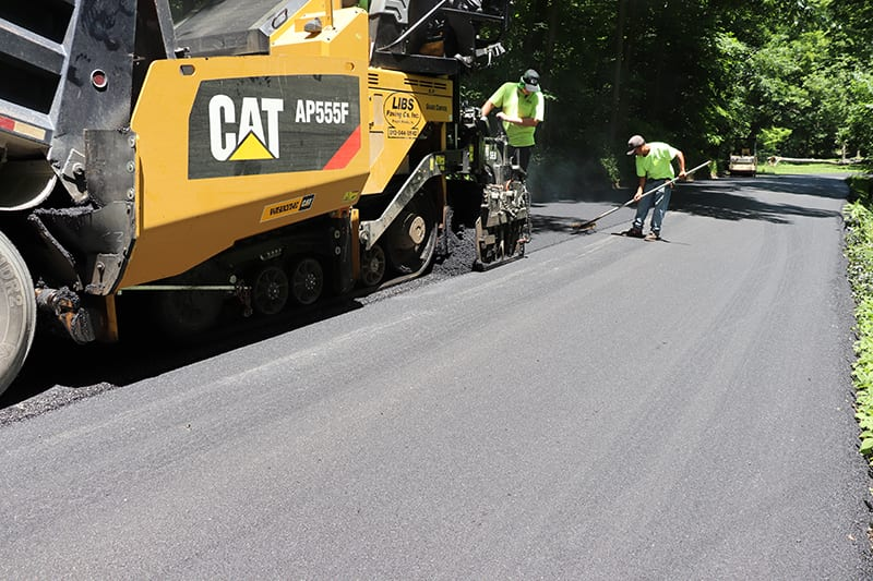 Libs Paving Co truck and workers paving asphalt