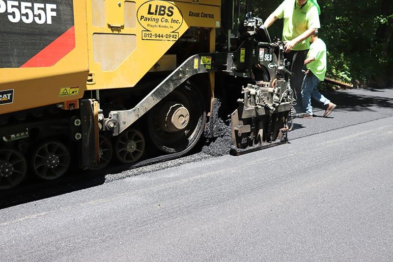 Close up of a Libs Paving truck pressing asphalt