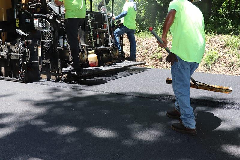 Construction workers paving asphalt