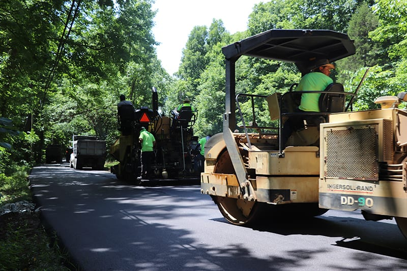 Construction workers operating machinery to pave an asphalt road
