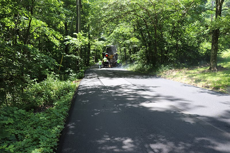 Construction workers at the end of a road working on an asphalt paving service