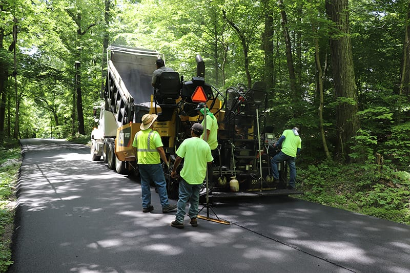 Construction workers paving a road with asphalt